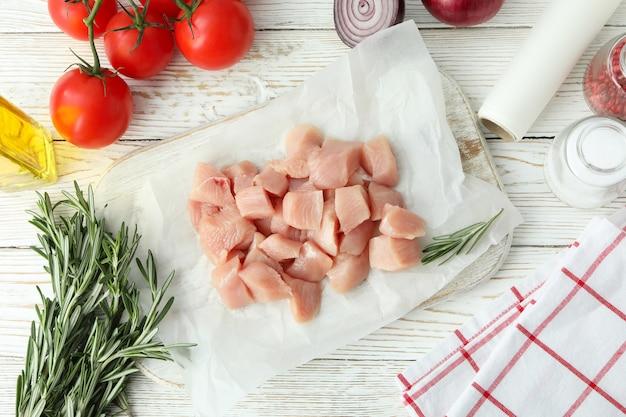 Concetto di cibo gustoso con fette di filetto di pollo crudo su fondo di legno bianco