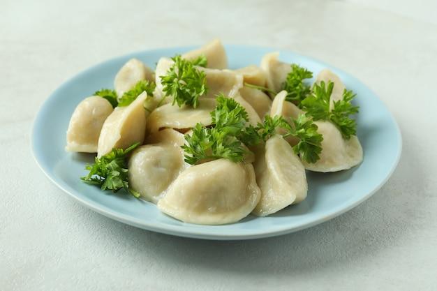 Concetto di cibo gustoso con vareniki o pierogi su tavola strutturata bianca