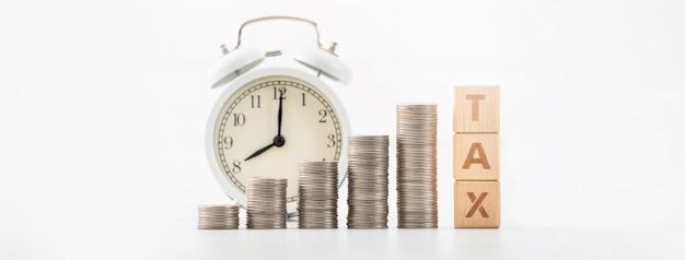 Concetto di stagione fiscale si avvicina con blocchi di legno, monete e sveglia su sfondo bianco.