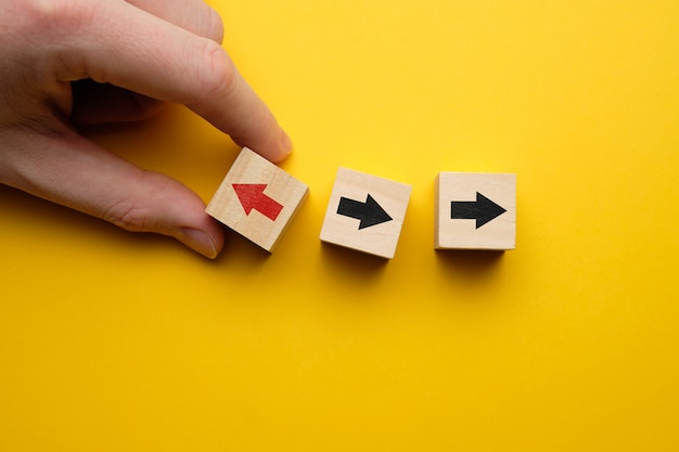 Il concetto di pensa diversamente - la mano tiene i cubi di legno con le frecce.