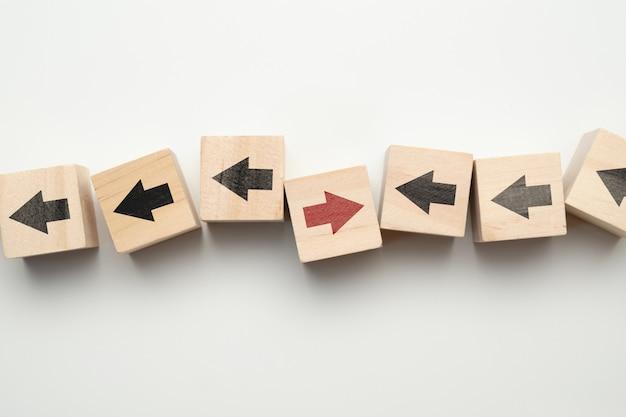 Il concetto di pensa diversamente - cubi di legno con le frecce.