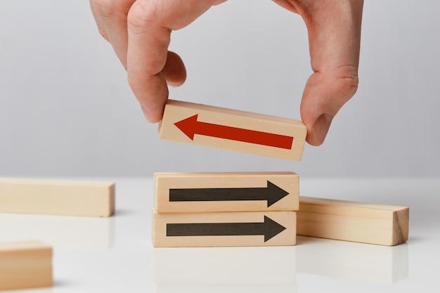 Concetto di pensiero diverso - la mano tiene un blocco di legno con una freccia.