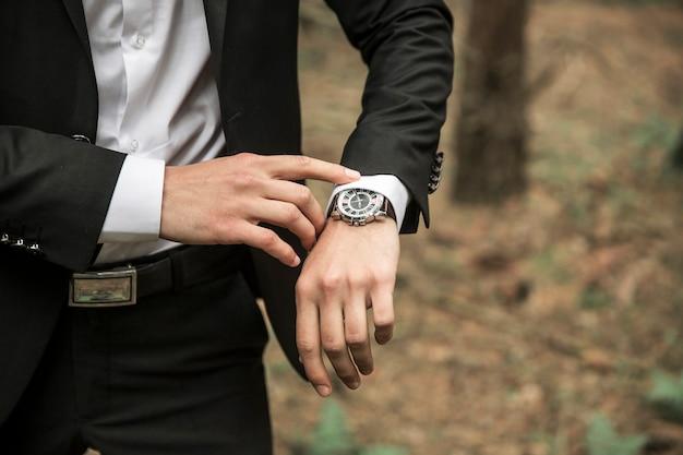 Concetto di tempo. uomo d'affari guardando orologio da polso