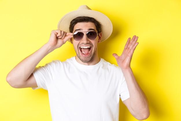 Concetto di turismo e vacanze primo piano dell'uomo sorpreso che grida di gioia godendosi le vacanze indossando ...