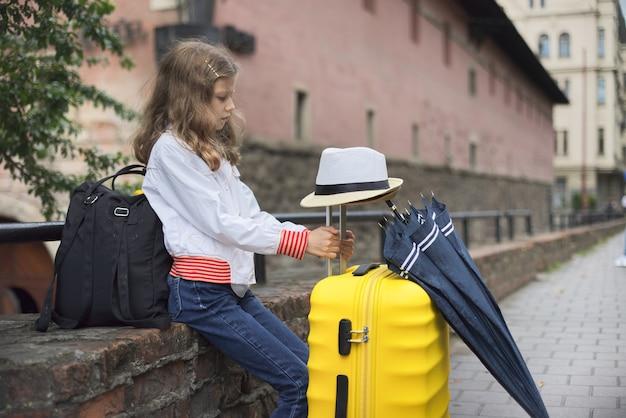 Concetto di turismo, viaggi, bambina con i bagagli