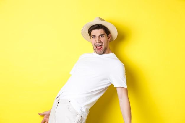 Concetto di turismo e vacanza. eccitato giovane turista che celebra, grida di gioia e balla, in piedi su sfondo giallo
