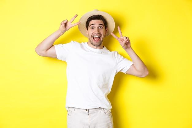 Concetto di turismo e vacanza. felice turista maschio in posa per una foto con segni di pace, sorridente eccitato, in piedi su sfondo giallo.