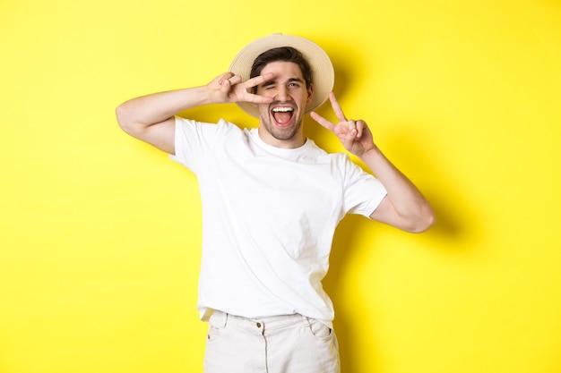 Concetto di turismo e vacanza. turista dell'uomo felice in posa per una foto con segni di pace, sorridente eccitato, in piedi su sfondo giallo.