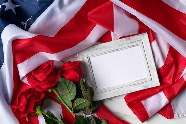 Concetto di giorno dell'indipendenza degli stati uniti o giorno della memoria. bandiera nazionale e rosa rossa su sfondo luminoso tavolo in marmo con cornice.