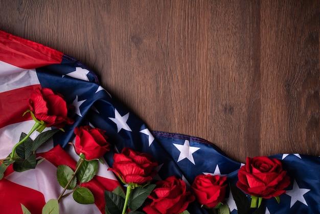 Concetto di giorno dell'indipendenza degli stati uniti o giorno della memoria. bandiera nazionale e rosa rossa su sfondo tavolo in legno scuro.