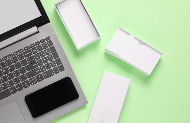 Il concetto di unboxing, techno blogging. scatola con nuovo smartphone, laptop su verde pastello