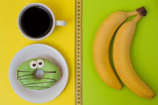 Concetto di mangiare e spuntino malsano. deliziosa ciambella e tazza di caffè forte isolate su banane gustose gialle e fresche isolate su sfondo verde. foto vista dall'alto