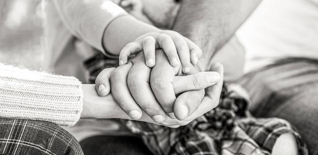 Concetto di unità, sostegno, protezione, felicità. primo piano della mano del bambino nei genitori. mani di padre, madre, tieni la mano piccolo bambino. bianco e nero.