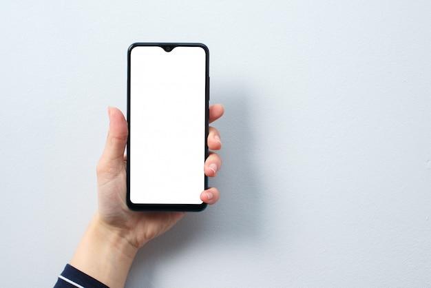 Concetto di utilizzo dello smartphone. smartphone con uno schermo bianco bianco nella mano di una donna.