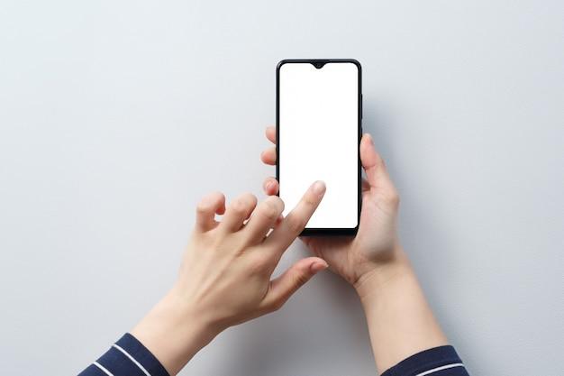 Concetto di utilizzo dello smartphone. smartphone con uno schermo bianco bianco nelle mani di una donna.