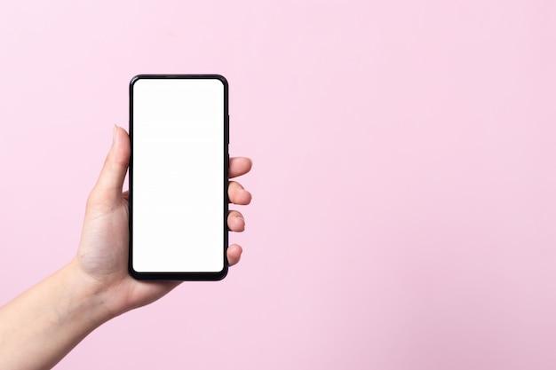 Concetto di utilizzo dello smartphone. uno smartphone con uno schermo bianco bianco nelle mani di una donna.