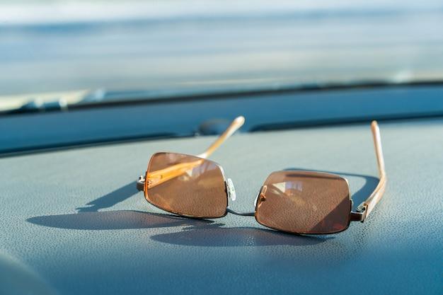 Il concetto di utilizzo di occhiali da sole durante il viaggio: occhiali da sole utilizzati in auto: close up occhiali da sole posizionati sul pannello dell'auto