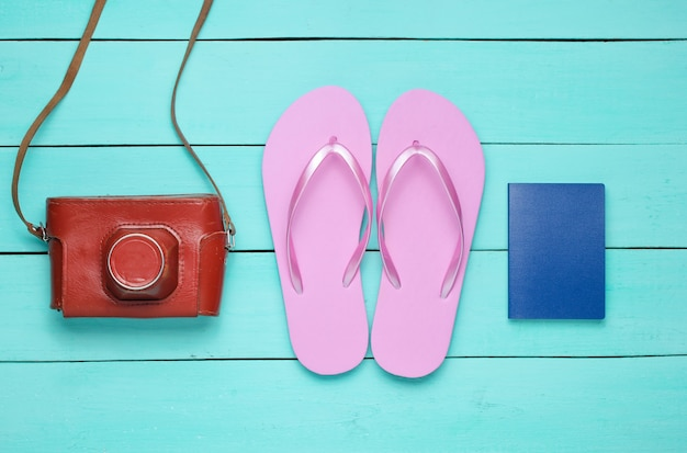 Concetto di vacanza sulla spiaggia, turismo. sfondo di viaggiatore estivo. infradito, fotocamera retrò, passaporto su fondo di legno blu.
