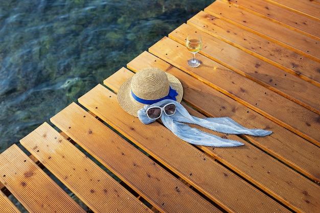 Il concetto di una vacanza al mare su un molo di legno è un cappello, occhiali da sole, un bicchiere di vino, vista dall'alto.