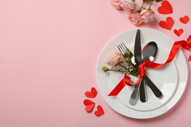 Concetto di san valentino con posate, rose e nastro su sfondo rosa