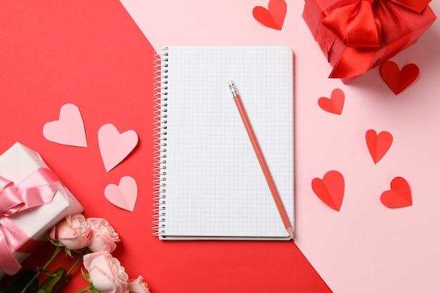 Concetto di san valentino con quaderno vuoto su due toni di sfondo