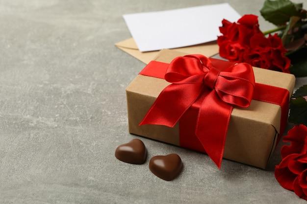 Concetto di san valentino con confezione regalo e rose su sfondo grigio