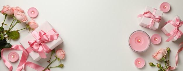 Concetto di san valentino con rose, scatole regalo e candele su sfondo bianco