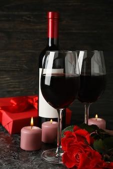 Concetto di san valentino con rose e vino sul tavolo nero smokey