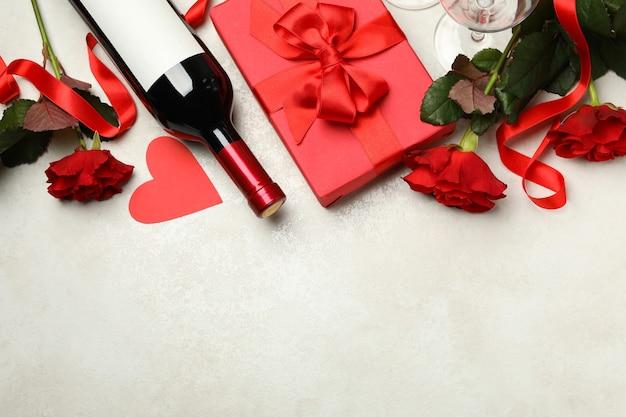 Concetto di san valentino con rose, vino e confezione regalo su sfondo bianco con texture