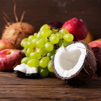 Concetto di cibo vegano con cocco, uva, peache e prugne
