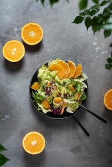 Concetto di cibo vegano con insalata verde e arance, vista dall'alto in basso con spazio di copia