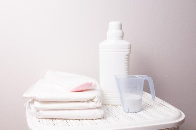 Il concetto di lavare biancheria bianca, candeggina e detersivo su un cesto della biancheria bianca