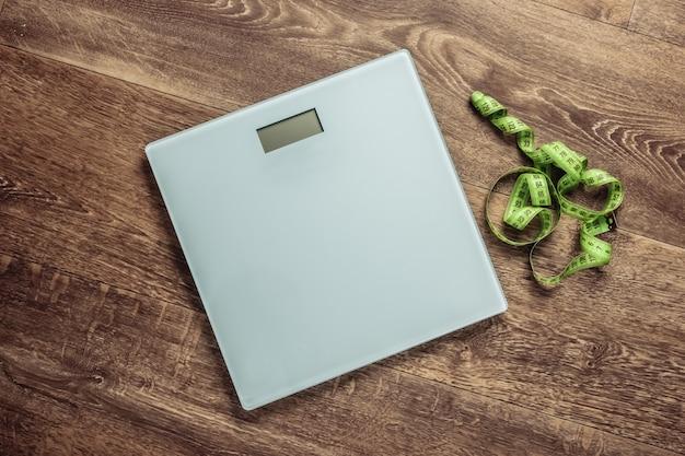 Il concetto di perdita di peso. bilance da pavimento con manubri, metro a nastro sul pavimento.