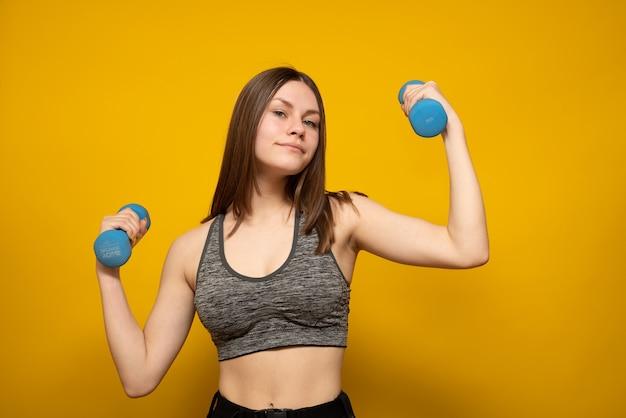 Il concetto di perdita di peso. una giovane donna snella tiene i manubri su uno sfondo giallo studio.