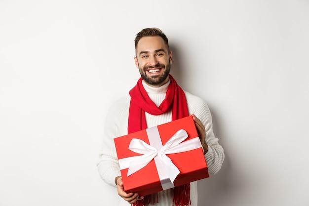 Concetto di vacanze invernali. uomo sorridente che ti fa un regalo, tiene un regalo e augura buon natale, in piedi su sfondo bianco