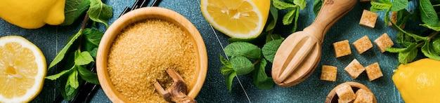 Concetto con ingredienti per limonata rinfrescante fatta in casa con succo di limone, zucchero di canna e menta su cemento vecchio.