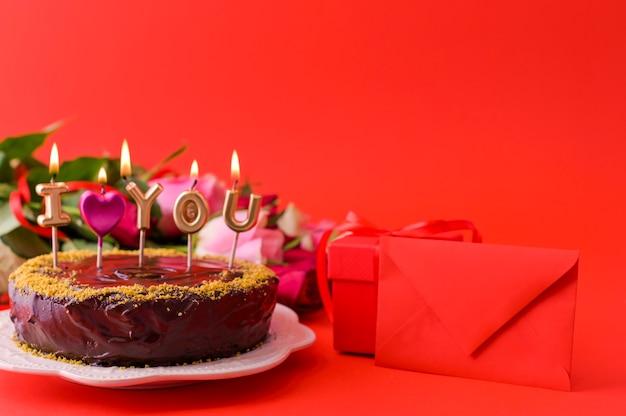 Concetto festa della donna o san valentino. rose fresche e confezione regalo su uno sfondo rosso e una torta al cioccolato con candele