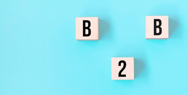 Parola di concetto b2b - business to business su cubi su un bellissimo sfondo blu. concetto di affari. copia spazio.