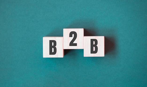 Parola di concetto b2b - business to business su cubi su un bellissimo sfondo verde. concetto di affari. copia spazio.