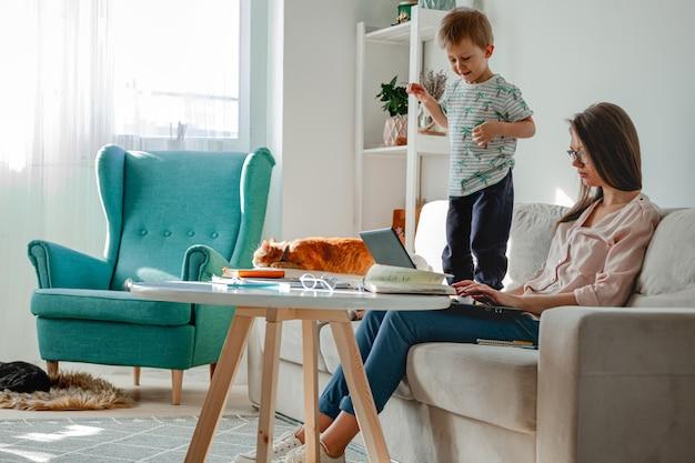 Concetto di lavoro a casa e educazione familiare a casa, madre che lavora con il laptop