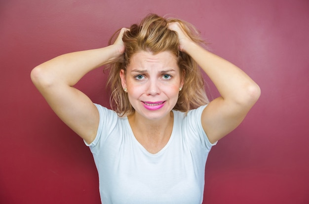 Concetto di preoccupazione, donna con entrambe le mani sulla testa