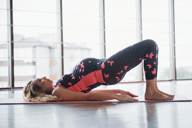 Concetto di yoga e gravidanza fitness. ritratto di un giovane modello di una donna incinta in via di sviluppo al chiuso.