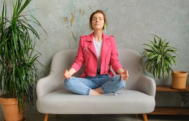 La giovane donna di concetto sitizen si rilassa e medita in un interno moderno. millenario per fuggire dal trambusto della città.