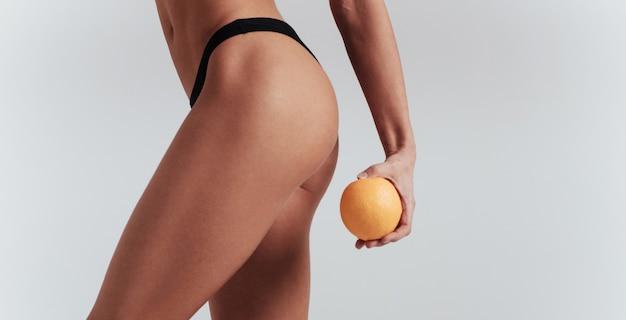 Concezione della dieta. foto di particelle di ragazza in biancheria intima nera in piedi al muro bianco e tenendo l'arancia.