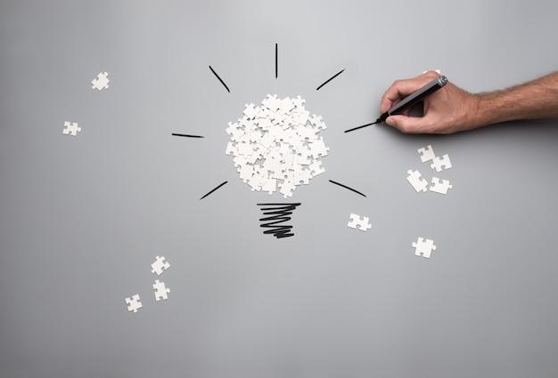 Immagine concettuale della visione e dell'idea di affari con un mucchio di pezzi di puzzle sparsi bianchi che formano una lampadina