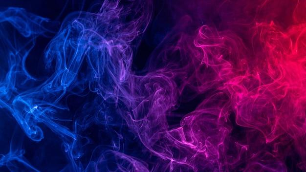 Immagine concettuale di fumo colorato di colore rosso e blu isolato su sfondo nero scuro, elemento di design del concetto di halloween.