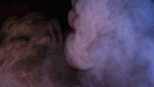 Immagine concettuale di fumo multicolore isolato su sfondo nero scuro e tavolo in legno. Foto Premium