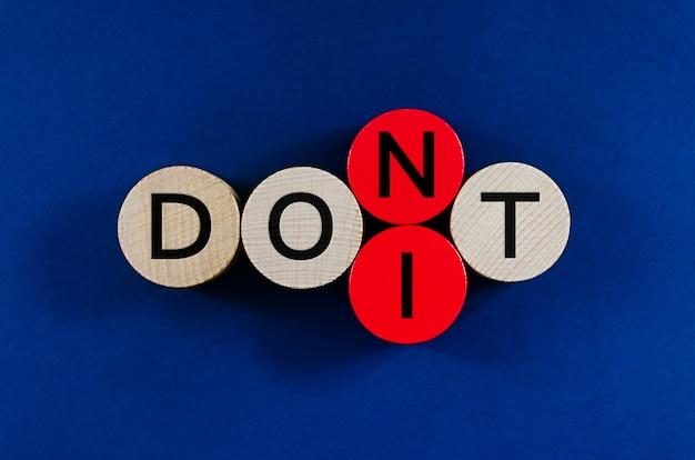 Immagine concettuale della parola non scrivere su pioli di legno con il secondo all'ultimo cerchio che sostituisce per scrivere la parola fallo.