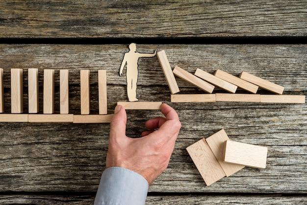 Concettuale di assicurazione sulla vita con la mano di un uomo che offre supporto attraverso una piattaforma stabile a un uomo di carta fermando il crollo causato dai mattoni di legno.