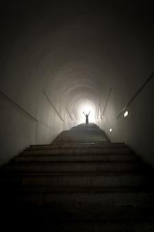Foto concettuale della persona in piedi alla fine del tunnel al raggio di luce con le mani alzate